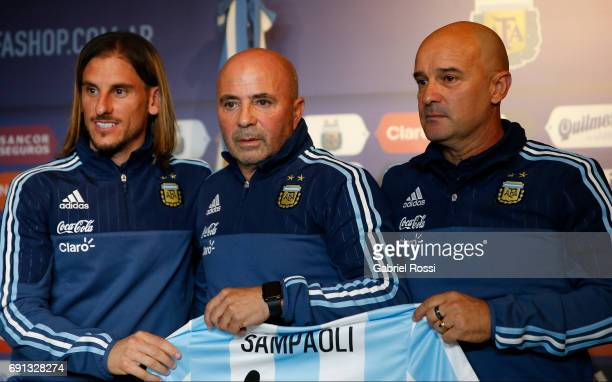 Jorge Sampaoli coach of Argentina poses with assistant coach Jorge Desio and Sebastian Beccacece during his presentation as new Argentina coach at...
