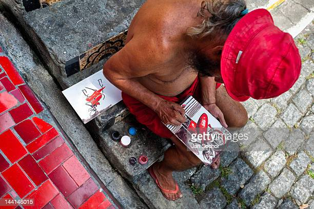 Jorge Selarón paints a picture in front of his house on Selaron's Stairs on February 13 2012 in Rio de Janeiro Brazil World famous staircase mostly...