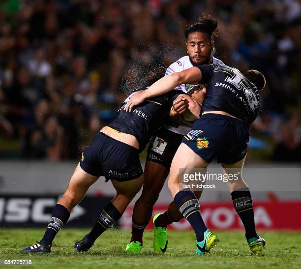 Jorge Taufua of the Sea Eagles is tackled by Shaun Fensom of the Cowboys during the round three NRL match between the North Queensland Cowboys and...