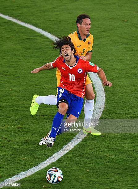 Jorge Valdivia of Chile falls after a challenge by Mark Milligan of Australia during the 2014 FIFA World Cup Brazil Group B match between Chile and...