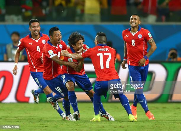 Jorge Valdivia of Chile is mobbed by his teammates after scoring the team's second goal during the 2014 FIFA World Cup Brazil Group B match between...
