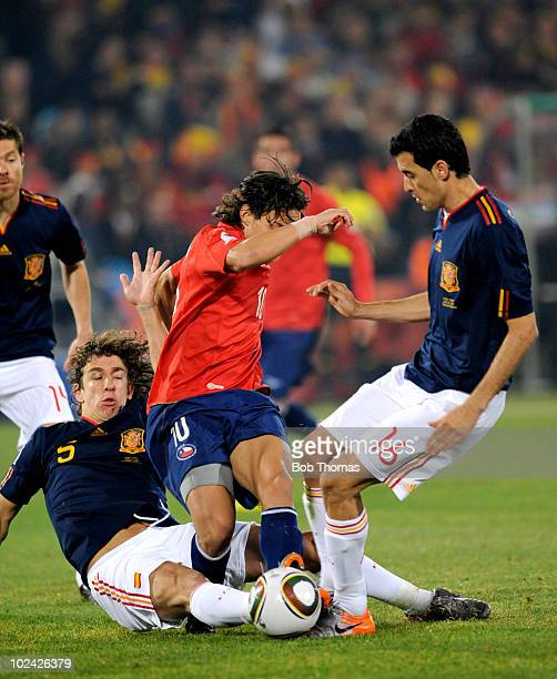 Jorge Valdivia of Chile is tackled by Carles Puyol and Sergio Busquets of Spain during the 2010 FIFA World Cup South Africa Group H match between...