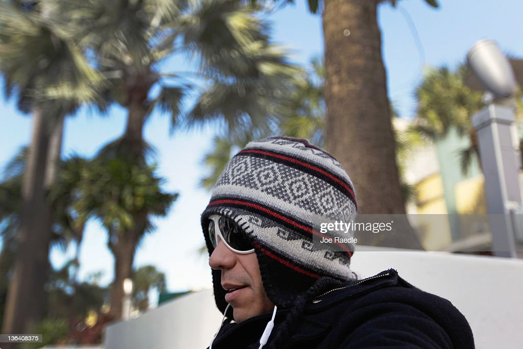 Jorge Verde bundles up against the cool weather as he sits at a table along Lincoln road mall on January 4, 2012 in Miami Beach, Florida. South Florida experienced one of the coolest days of the winter season last night but temperatures are expected to warm up.