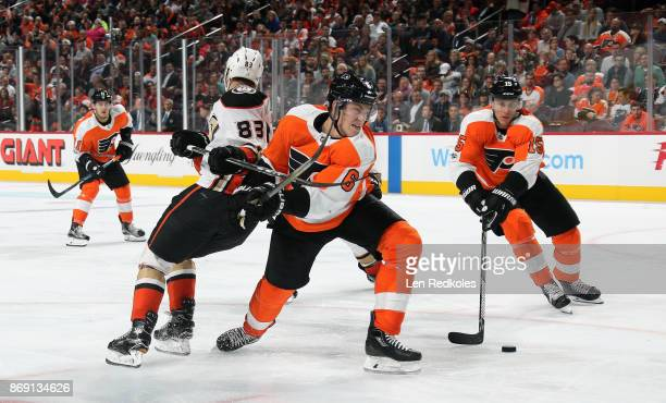 Jori Lehtera and Travis Sanheim of the Philadelphia Flyers battle for control of the puck against Kalle Kossila of the Anaheim Ducks on October 24...