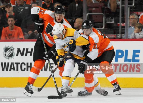 Jori Lehtera and Valtteri Filppula of the Philadelphia Flyers battle for the loose puck with Calle Jarnkrok of the Nashville Predators on October 19...