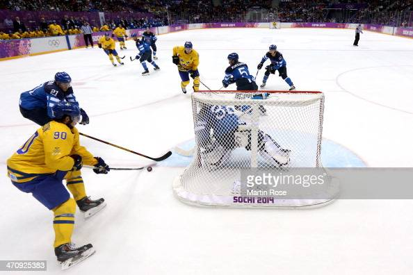 Jori Lehtera of Finland and Marcus Johansson of Sweden compete for the puck beside the net during the Men's Ice Hockey Semifinal Playoff on Day 14 of...