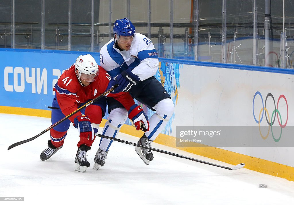 Jori Lehtera #21 of Finland and Patrick Thoresen #41 of Norway fight for a loose puck in the first period during the Men's Ice Hockey Preliminary Round Group B game on day seven of the Sochi 2014 Winter Olympics at Shayba Arena on February 14, 2014 in Sochi, Russia.