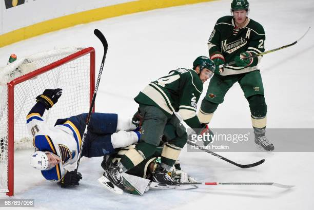 Jori Lehtera of the St Louis Blues crashes into the net after tripping over Devan Dubnyk and Matt Dumba of the Minnesota Wild as Ryan Suter looks on...