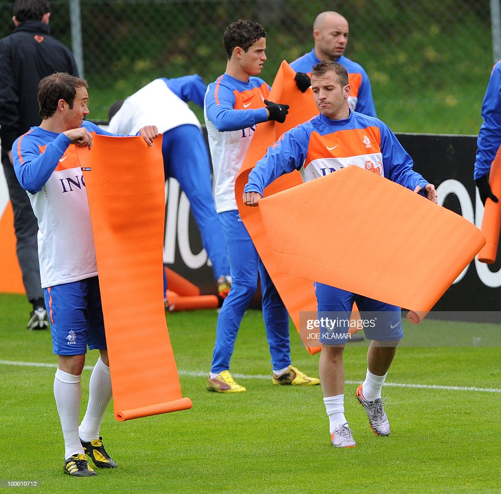 Joris Mathijsen (left) and Rafael Van Der Vaart (r) bring material as they warm u^p during the first Netherland's team's practice on the opening of their training camp in the Tyrolian village of Seefeld in Austria on 20 May 2010 in preparation for the 2010 FIFA World cup hosted by South Africa from June 11 to July 11.