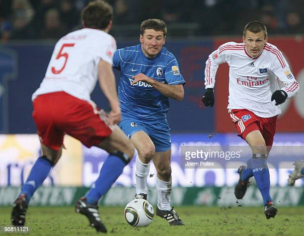 Joris Mathijsen and Robert Tesche of Hamburg and Stefan Reisinger of Freiburg battle for the ball during the Bundesliga match between Hamburger SV...