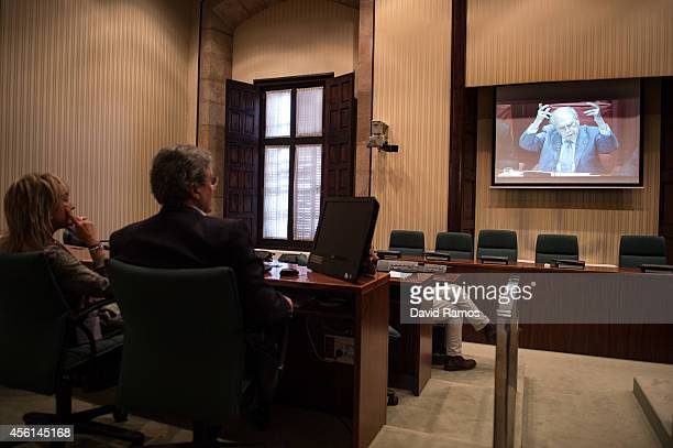 Jornalist watch to Former Catalan President Jordi Pujol on a screen as he speaks to the members of the parliament on September 26 2014 in Barcelona...