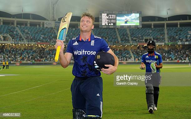 Jos Buttler of England raises his bats as he leaves the field after making 116 not out during the 4th One Day International between Pakistan and...