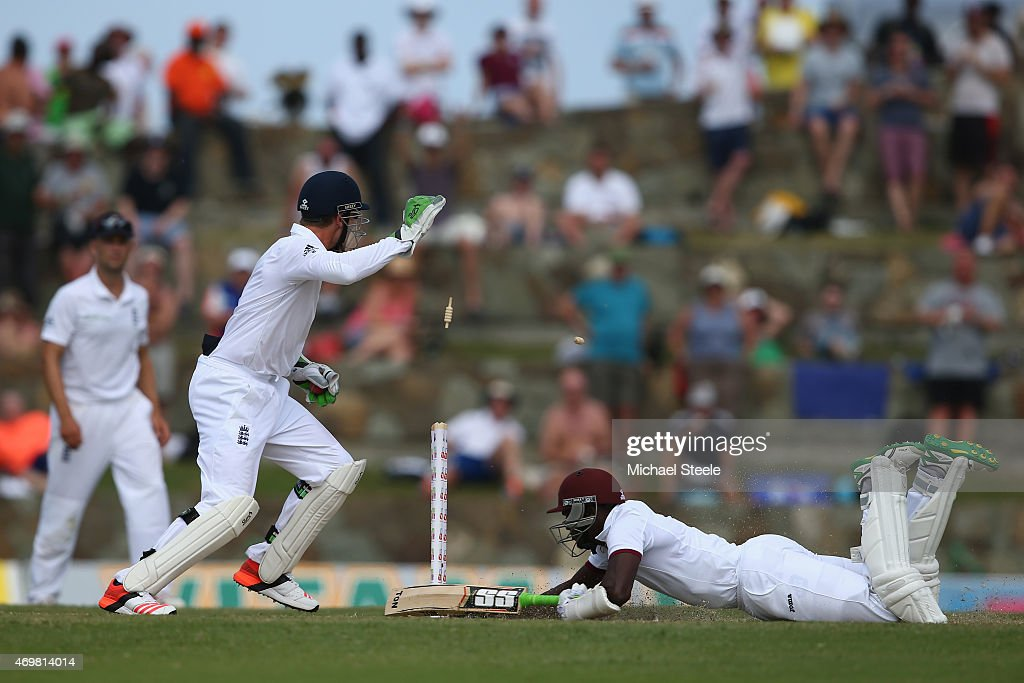 Jos Buttler (L) of England whips the bails off to run out Jerome Taylor of West Indies during day three of the 1st Test match between West Indies and England at the Sir Vivian Richards Stadium on April 15, 2015 in Antigua, Antigua and Barbuda.