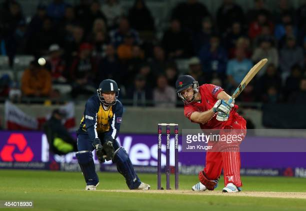 Jos Buttler of Lancashire Lightning hits out with Tim Ambrose of Birmingham Bears looking on during the Natwest T20 Blast Final match between...