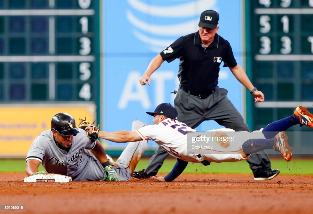 Jose Abreu #79 of the Chicago White Sox avoids the tag of Jose Altuve #27 of the Houston Astros in the third inning as second base umpire Mike Everitt looks in at Minute Maid Park on September 21, 2017 in Houston, Texas.