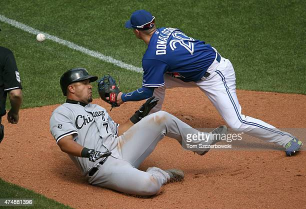 Jose Abreu of the Chicago White Sox hits a triple as he slides into third base in the tenth inning during MLB game action against the Toronto Blue...