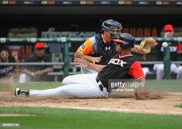Jose Abreu of the Chicago White Sox slides in to score a run in the 8th inning as John Hicks of the Detroit Tigers takes the throw at Guaranteed Rate...