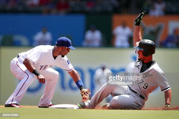 Jose Abreu of the Chicago White Sox slides into second base against Elvis Andrus of the Texas Rangers in the top of the first inning at Globe Life...