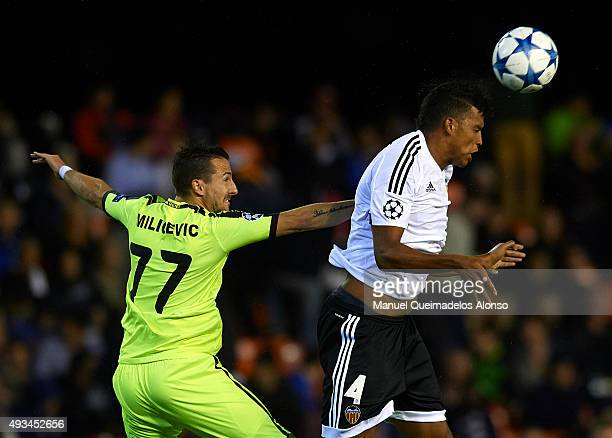 Jose Aderlan Santos of Valencia competes for the ball with Danijel Milicevic of Gent during the UEFA Champions League Group H match between Valencia...