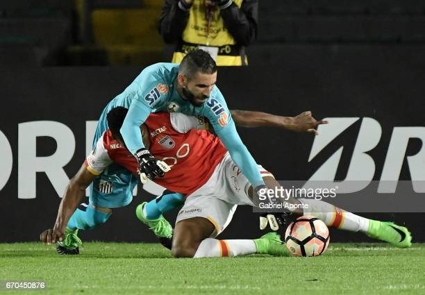 Jose Adolfo Valencia of Santa Fe struggles for the ball with Vanderlei goalkeeper of Santos during a group stage match between Independiente Santa Fe...