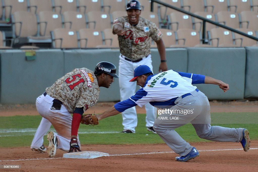 Jose Alberto Martines (L) of Venezuela slides safe at third base against Puerto Rico during their 2016 Caribbean baseball series game on February 6, 2016 in Santo Domingo, Dominican Republic. AFP PHOTO/YAMIL LAGE / AFP / YAMIL LAGE