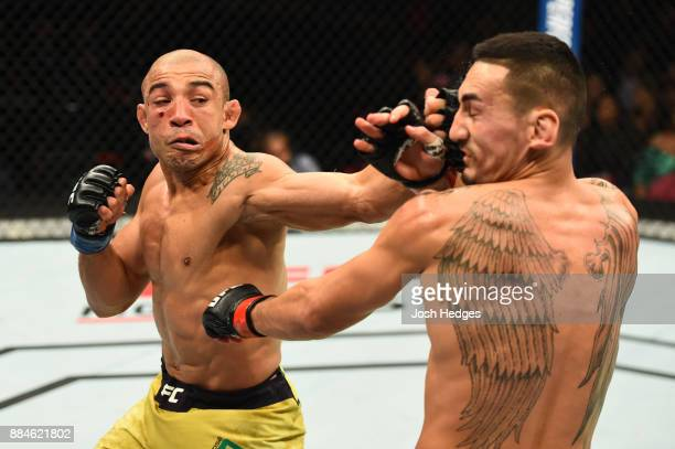 Jose Aldo of Brazil punches Max Holloway in their UFC featherweight championship bout during the UFC 218 event inside Little Caesars Arena on...