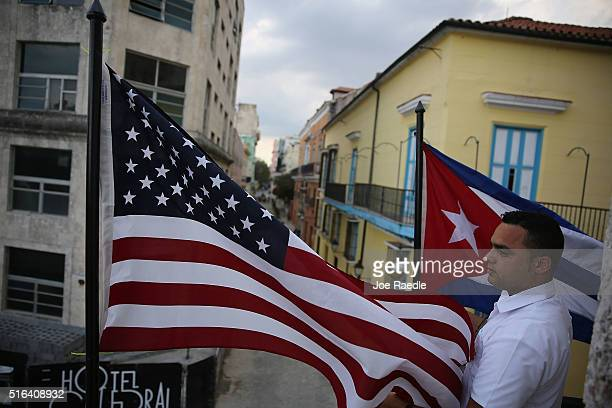Jose Alfredo stands near an American flag and Cuban flag hanging from a restaurant in Old Havana as Cuba prepares for the visit of US President...
