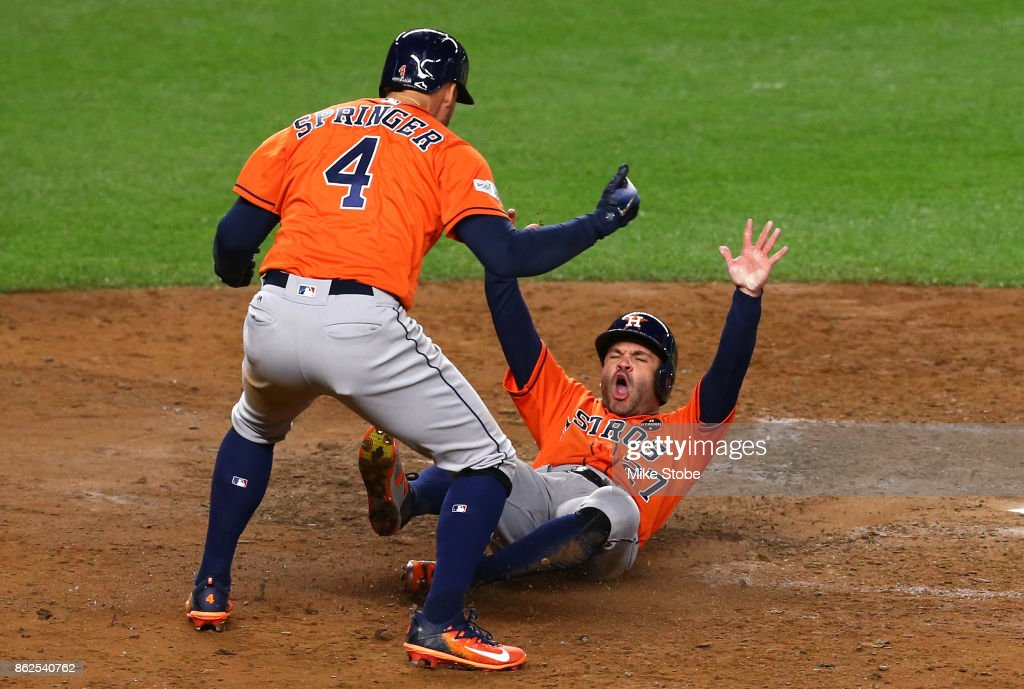 Jose Altuve #27 and George Springer #4 of the Houston Astros celebrate after scoring on a Yuli Gurriel #10 3-run double during the sixth inning against the New York Yankees in Game Four of the American League Championship Series at Yankee Stadium on October 17, 2017 in the Bronx borough of New York City.
