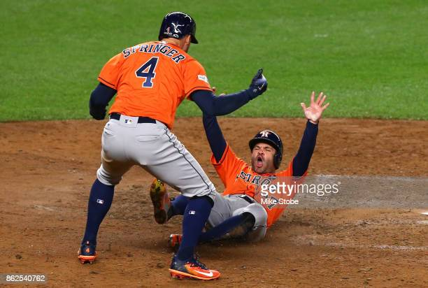 Jose Altuve and George Springer of the Houston Astros celebrate after scoring on a Yuli Gurriel 3run double during the sixth inning against the New...