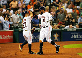 Jose Altuve and Jon Singleton of the Houston Astros celebrate after Singleton hit a solo home run against the Los Angeles Angels of Anaheim in the...