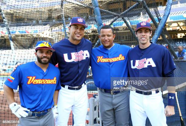 Jose Altuve and Miguel Cabrera of Team Venezuela pose for a photo with Christian Yelich and Giancarlo Stanton of Team USA before Game 2 of Pool F of...