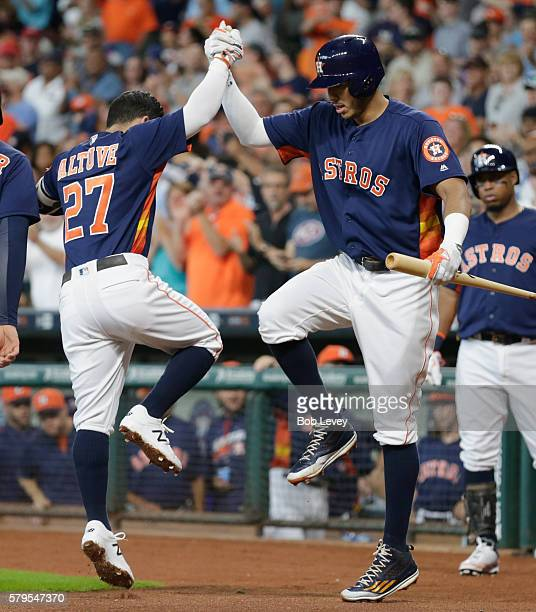 Jose Altuve of the Houston Astros and Carlos Correa celebrate after Altuve's three run home run in the first inning against the Los Angeles Angels of...
