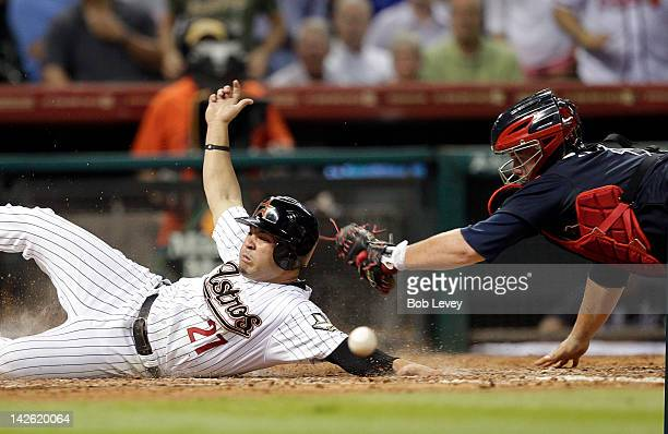 Jose Altuve of the Houston Astros avoids the tag at home as catcher Brian McCann of the Atlanta Braves can't handle the throw after a triple by...