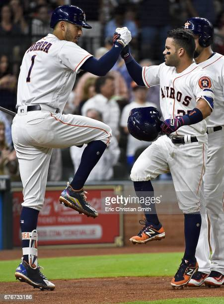 Jose Altuve of the Houston Astros celebrates his tworun home run with Carlos Correa during the fourth inning against the Texas Rangers at Minute Maid...