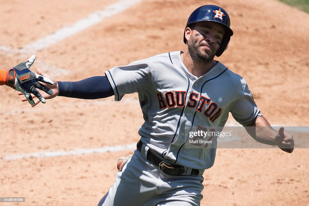 <a gi-track='captionPersonalityLinkClicked' href=/galleries/search?phrase=Jose+Altuve&family=editorial&specificpeople=7934195 ng-click='$event.stopPropagation()'>Jose Altuve</a> #27 of the Houston Astros celebrates with a teammate as he scores on a sacrifice fly by Luis Valbuena during the third inning of the game against the Los Angeles Angels of Anaheim as at Angel Stadium of Anaheim on June 29, 2016 in Anaheim, California.