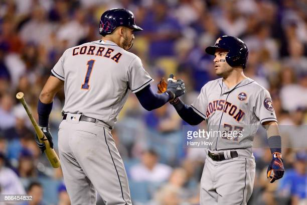 Jose Altuve of the Houston Astros celebrates with Carlos Correa after hitting a solo home run during the tenth inning against the Los Angeles Dodgers...