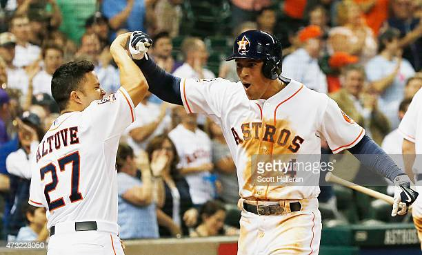 Jose Altuve of the Houston Astros greets teammate George Springer of the Houston Astros after Springer hit a solo home run in the eighth inning of...