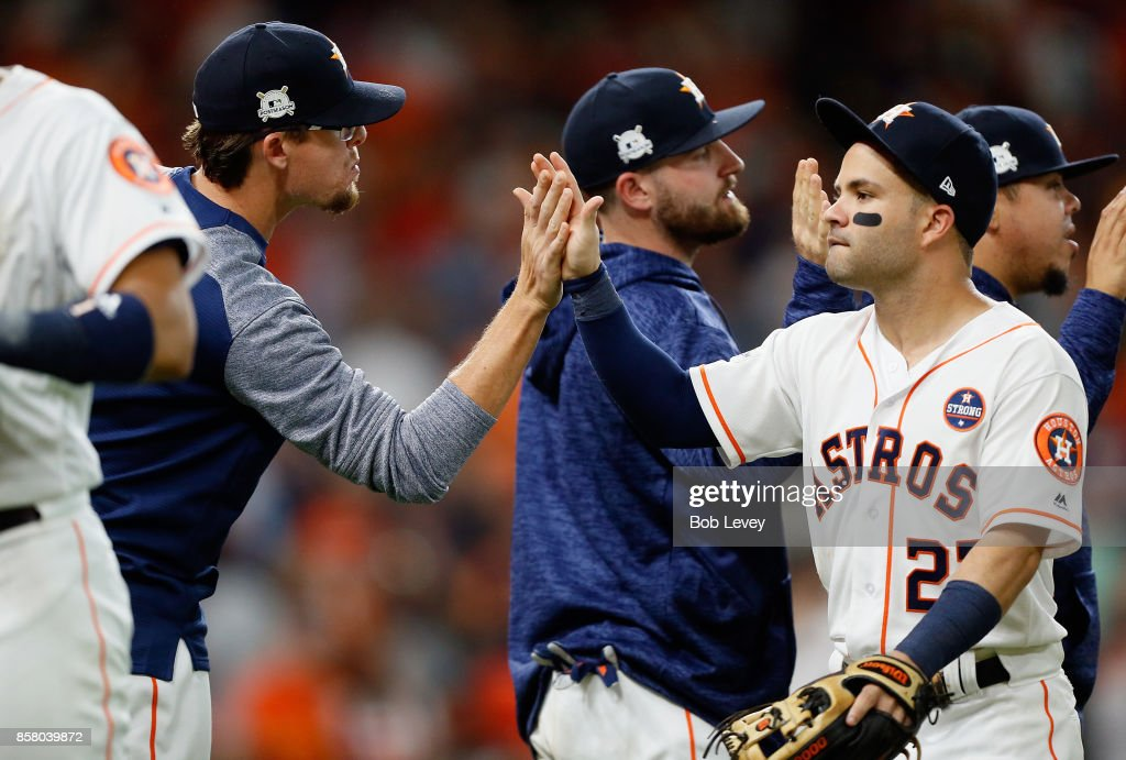Jose Altuve #27 of the Houston Astros high fives Tyler Clippard #19 after defeating the Boston Red Sox 8-2 to win game one of the American League Division Series at Minute Maid Park on October 5, 2017 in Houston, Texas.