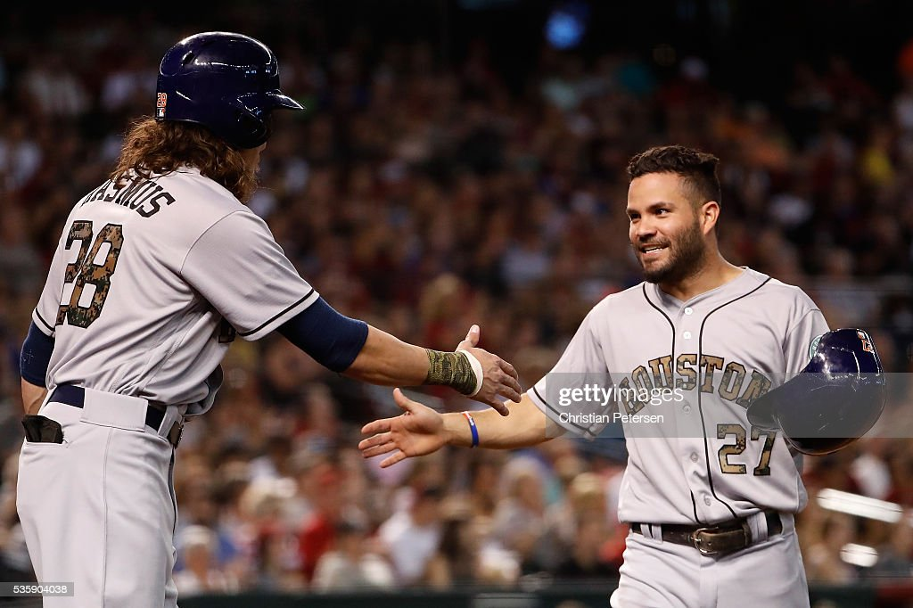 Jose Altuve #27 of the Houston Astros high-fives Colby Rasmus #28 after Altuve scored a second-inning run against the Arizona Diamondbacks during the MLB game at Chase Field on May 30, 2016 in Phoenix, Arizona.