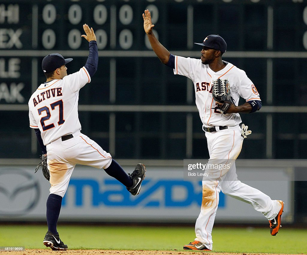 Jose Altuve #27 of the Houston Astros high-fives Dexter Fowler #21 after defeating the New York Yankees 6-2 at Minute Maid Park on April 1, 2014 in Houston, Texas.