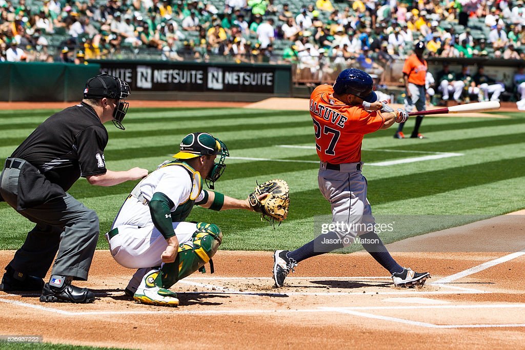 Jose Altuve #27 of the Houston Astros hits a home run in front of Stephen Vogt #21 of the Oakland Athletics and umpire Todd Tichenor #13 during the first inning at the Oakland Coliseum on May 1, 2016 in Oakland, California.