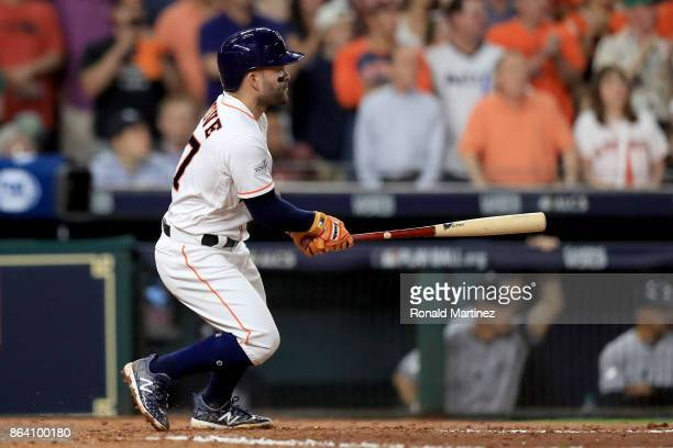 Jose Altuve of the Houston Astros hits a single to left field to score Evan Gattis and Brian McCann against Luis Severino of the New York Yankees...