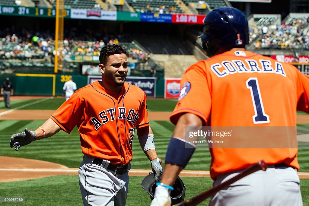 Jose Altuve #27 of the Houston Astros is congratulated by Carlos Correa #1 after hitting a home run against the Oakland Athletics during the first inning at the Oakland Coliseum on May 1, 2016 in Oakland, California.