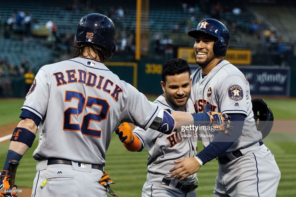 Jose Altuve #27 of the Houston Astros is congratulated by George Springer #4 and Josh Reddick #22 after hitting a two-run home run against the Oakland Athletics during the first inning at the Oakland Coliseum on September 8, 2017 in Oakland, California.