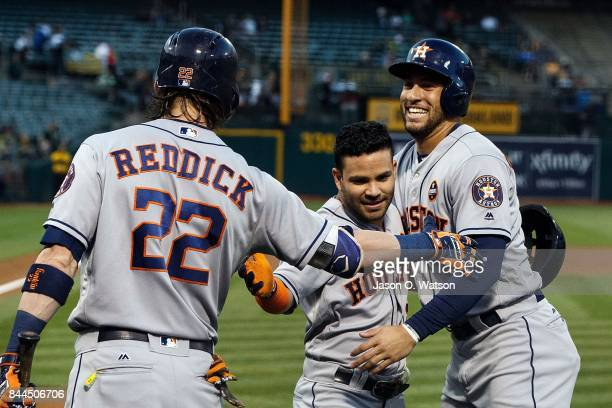 Jose Altuve of the Houston Astros is congratulated by George Springer and Josh Reddick after hitting a tworun home run against the Oakland Athletics...