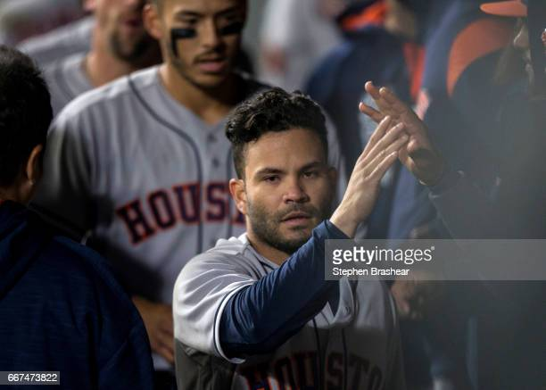 Jose Altuve of the Houston Astros is congratulated by teammates in the dugout after scoring on a single by Carlos Beltran of the Houston Astros off...