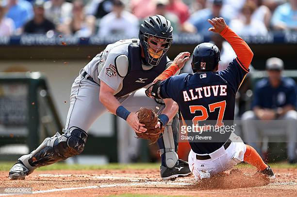 Jose Altuve of the Houston Astros is tagged out at home plate by James McCann of the Detroit Tigers during a spring training game at Osceola County...