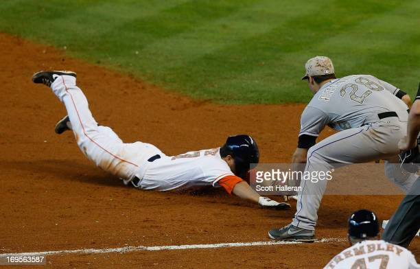 Jose Altuve of the Houston Astros is tagged out at third base in the sixth inning by Nolan Arenado of the Colorado Rockies at Minute Maid Park on May...