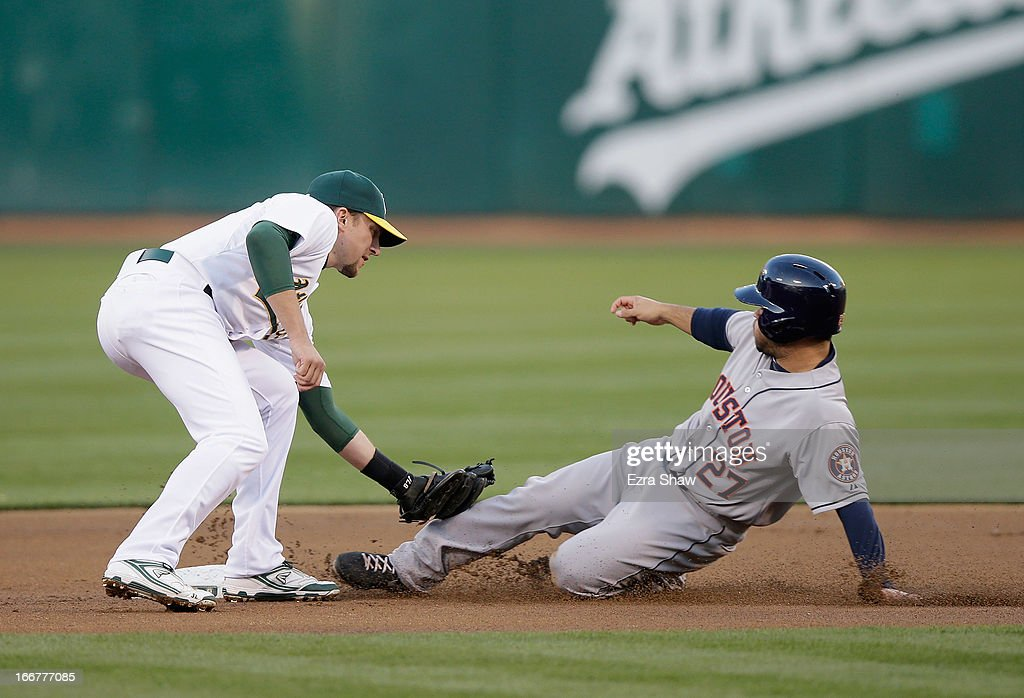 Jose Altuve #27 of the Houston Astros is tagged out by Jed Lowrie #8 of the Oakland Athletics on a steal attempt in the first inning at O.co Coliseum on April 16, 2013 in Oakland, California.