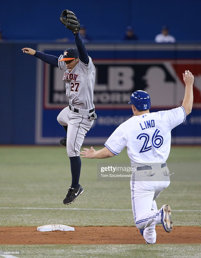 Jose Altuve #27 of the Houston Astros jumps but cannot come up with a high throw on a throwing error in the fifth inning during MLB game action as Adam Lind #26 of the Toronto Blue Jays slides on April 9, 2014 at Rogers Centre in Toronto, Ontario, Canada.